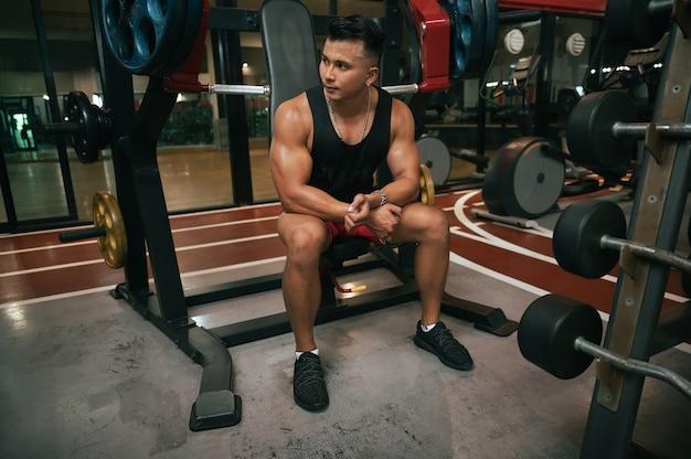 Homem fitness com máquina de treino no ginásio