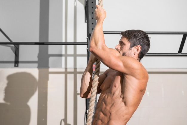 Homem fitness fazendo exercício de escalada na corda na academia