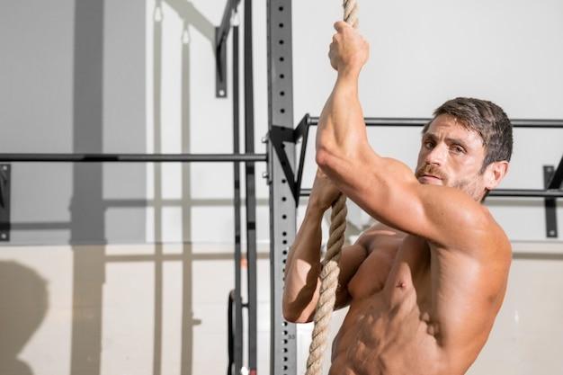 Homem fitness fazendo exercício de escalada na corda no ginásio