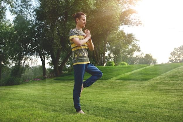 Homem fitness fazendo exercícios em uma perna isolado no parque
