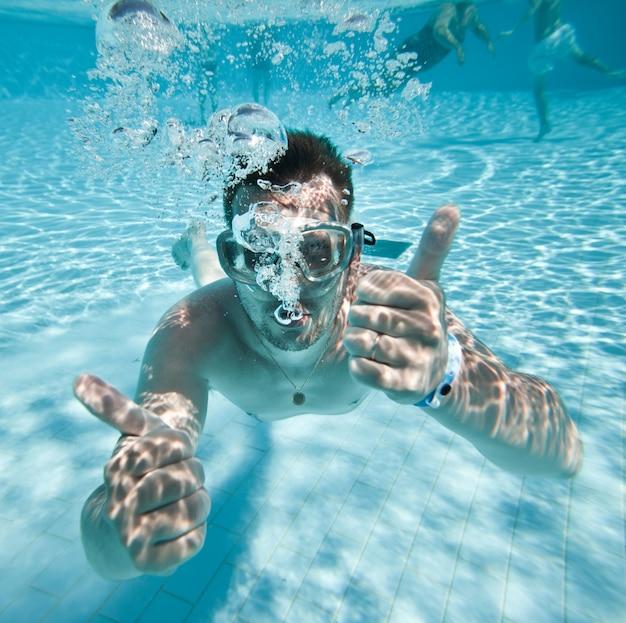 Homem flutua debaixo d'água na piscina