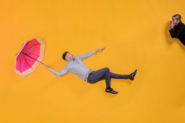 Homem flutuando no ar com um guarda-chuva