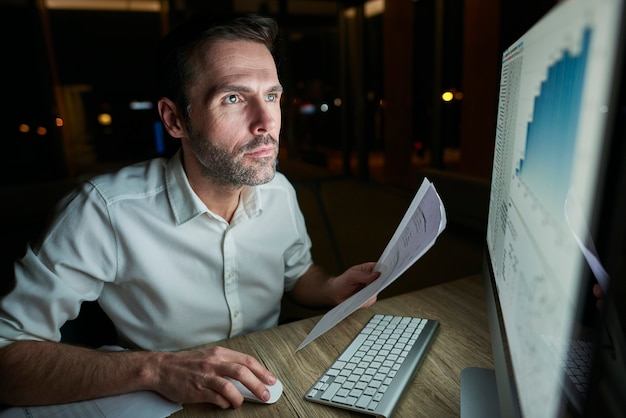 Homem focado com documento usando computador