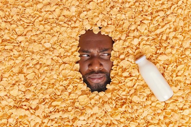 Homem focado de lado olha seriamente para a garrafa de leite cercada por flocos de milho espetados na comida