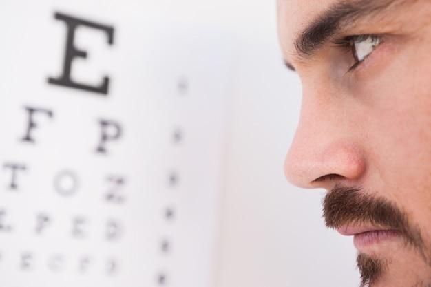 Homem focado em cartas de teste de olho