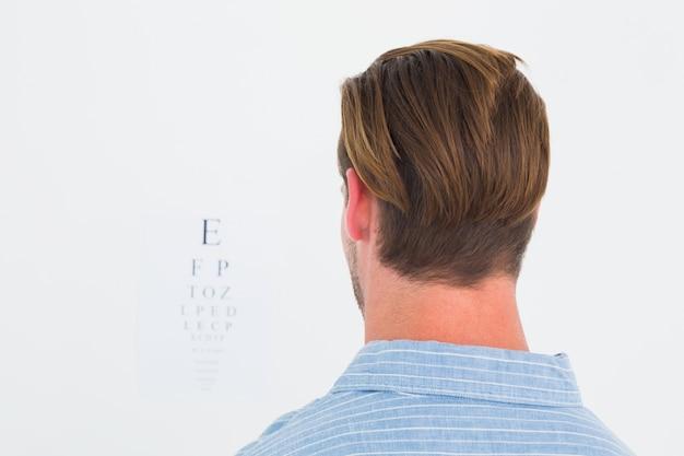 Homem focado em terno em letras de teste de olho