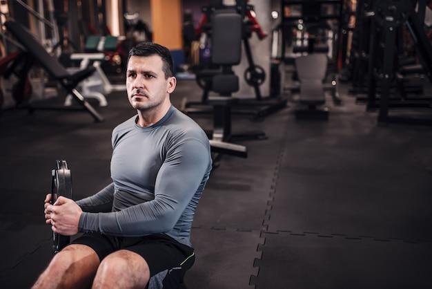 Homem focado no sportswear treinamento abs com pesos.