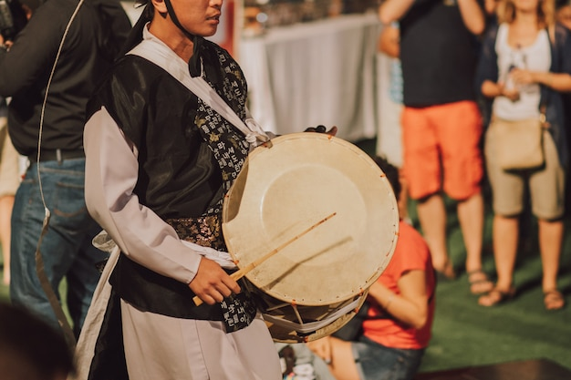 Homem folk coreano tocando com instrumento tradicional ao ar livre Foto Premium