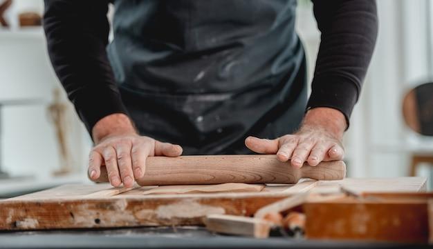 Homem formando molde de argila de oleiro