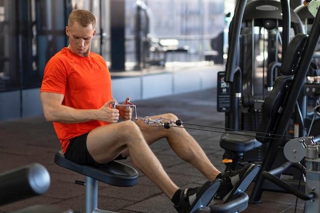 Homem forte atleta bombeando os músculos no ginásio. treino de cara de músculo. exercícios para imprensa, bíceps, pernas.