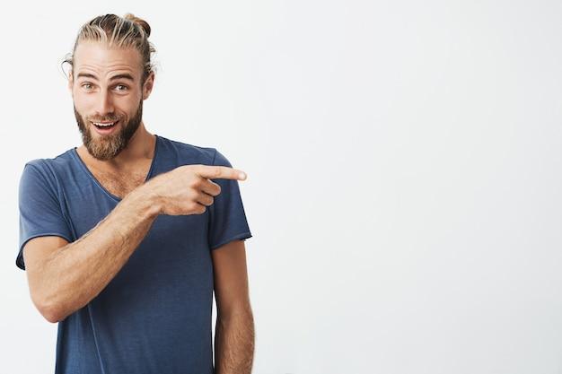 Homem forte bonito com um penteado bonito e barba na camisa azul, apontando um lado com a expressão do rosto surpreso