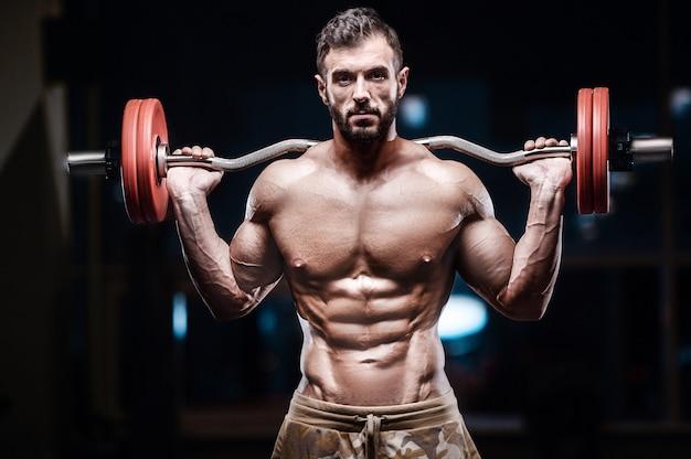 Homem forte de fisiculturista bombeando os músculos abdominais