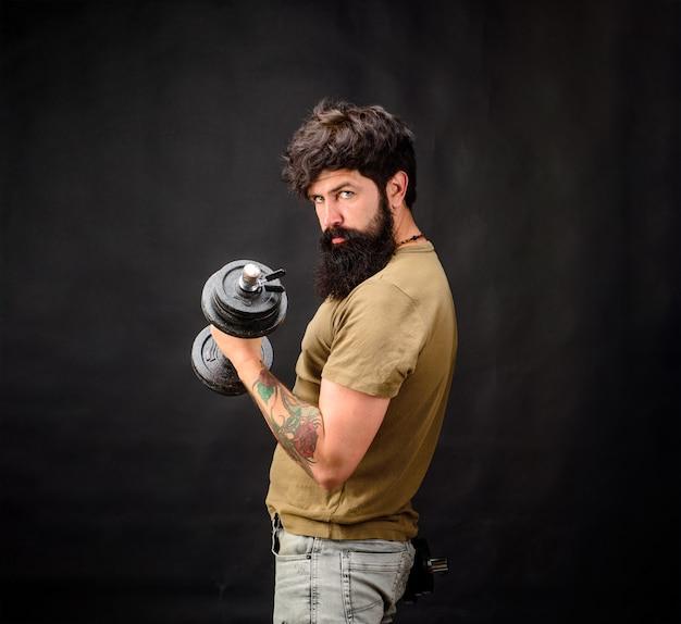 Homem forte de fitness segura halteres desportista musculoso com halteres treinando no ginásio bonito atleta