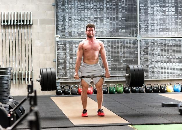 Homem forte deadlifter treinando com pesos pesados