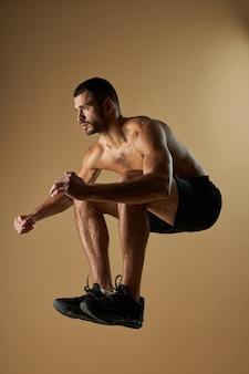 Homem forte e adorável atleta se aquecendo enquanto se exercita na academia