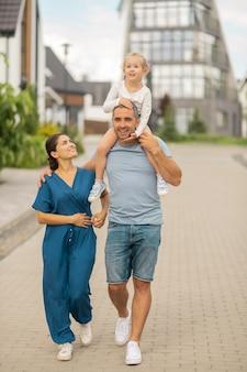 Homem forte e amoroso. homem forte e amoroso se sentindo feliz abraçando sua esposa e tendo a filha no pescoço