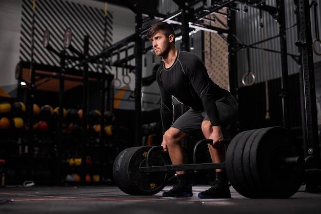 Homem forte e apto treinando com pesos pesados no ginásio, jovem cara caucasiano em roupa esportiva preta faz exercícios de treino sozinho. fitness, conceito de esporte