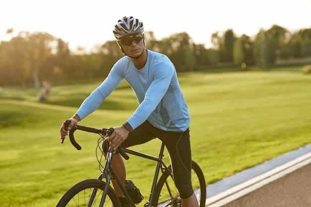 Homem forte e atlético em roupas esportivas e capacete protetor em pé com sua bicicleta na estrada