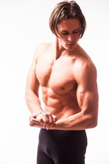 Homem forte e atlético flexionando o tronco isolado na parede branca