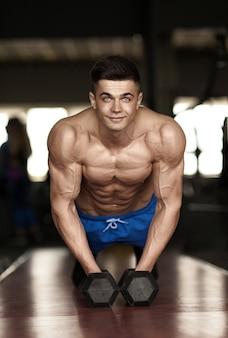 Homem forte e bonito fazendo flexões em halteres em uma academia como exercício de musculação, treinando seus músculos