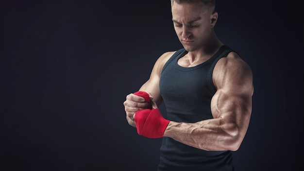 Homem forte e caucasiano envolvendo as mãos em fundo preto o homem está envolvendo as mãos com envoltórios de boxe vermelho isoladas no fundo preto fortes mãos e punhos, prontos para o treinamento e exercícios ativos