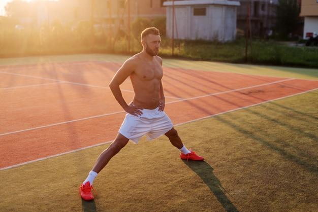 Homem forte e desportivo, esticando as pernas antes do treino. de pé no campo de ténis na manhã quente de verão.