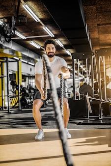 Homem forte e feliz ativo fazendo exercícios de corda de batalha no moderno ginásio ensolarado.