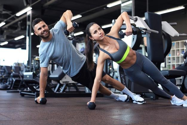 Homem forte e mulher segurando halteres em posição de prancha no ginásio.