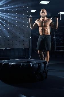 Homem forte e musculoso bonito segurando uma grande marreta atrás do pescoço.