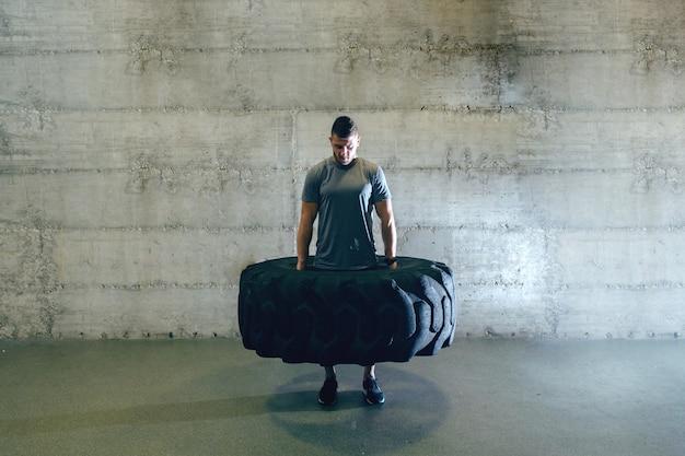Homem forte e musculoso no sportswear, levantando o pneu em pé na frente da parede no ginásio cross-fit.