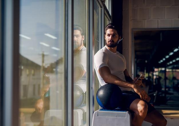Homem forte e musculoso sentado perto da janela com o celular na mão e uma grande bola ao lado dele e olhando para longe.