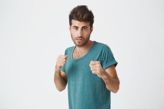 Homem forte e resoluto de camiseta azul com barba em pé em uma posição de luta em uma parede branca. estudante do sexo masculino se preparando para defender sua honra
