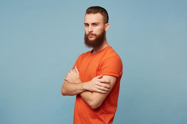 Homem forte e sério homem moderno com barba e um corte de cabelo da moda vestindo uma camiseta vermelha fica com os braços cruzados