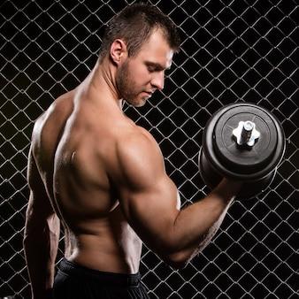 Homem forte e seus músculos com um haltere