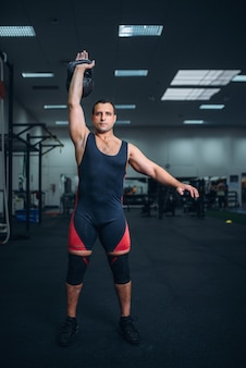 Homem forte em roupas esportivas fazendo exercícios com kettlebell