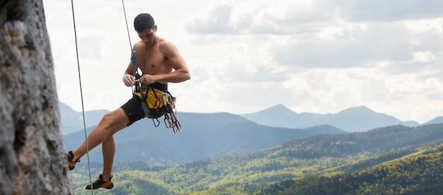 Homem forte escalando montanha com equipamento de segurança