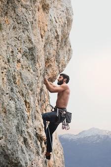 Homem forte escalando uma montanha