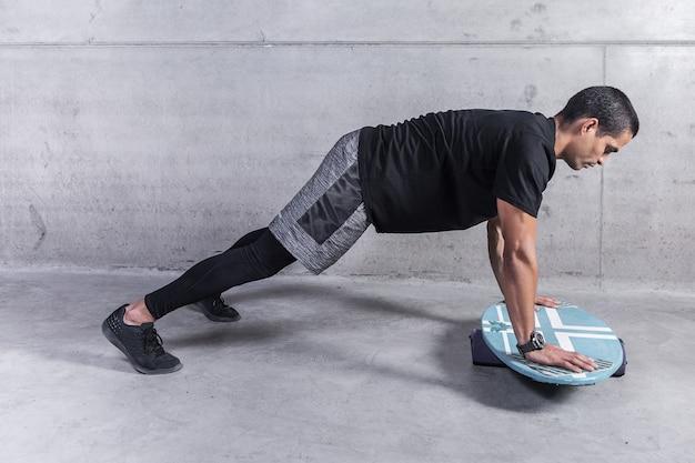 Homem forte, exercitar-se com placa de equilíbrio