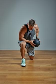 Homem forte fazendo exercício com bola med. foto do corpo perfeito do homem na parede cinza. força e motivação.