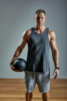 Homem forte fazendo exercício com bola med. foto do corpo perfeito do homem no espaço cinzento. força e motivação.