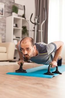 Homem forte fazendo flexões na esteira de ioga durante o auto-isolamento.