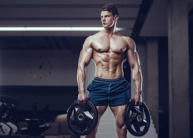 Homem forte fisiculturista aumentando os músculos abdominais