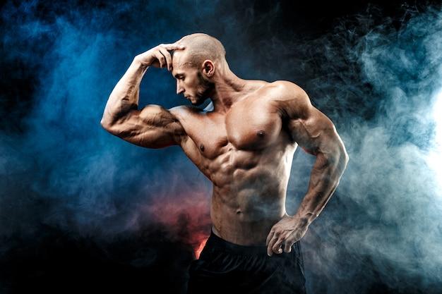 Homem forte fisiculturista com abs perfeito, ombros, bíceps, tríceps, peito