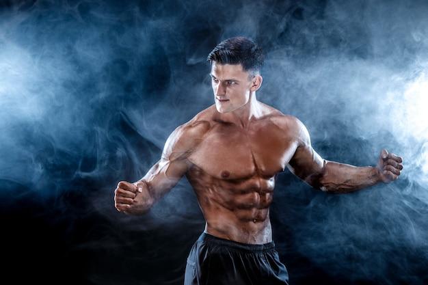 Homem forte fisiculturista com abs perfeito, ombros, bíceps, tríceps, peito.