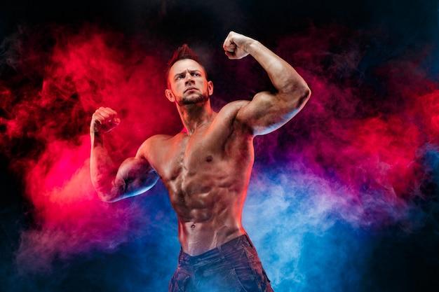Homem forte fisiculturista em calças militares com abs perfeito, ombros, bíceps, tríceps, peito