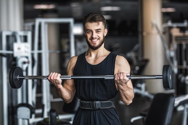 Homem forte, fisiculturista em roupas esportivas com halteres em uma academia, se exercitando com uma barra