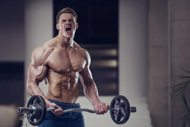 Homem forte fisiculturista estimulando os músculos do bíceps
