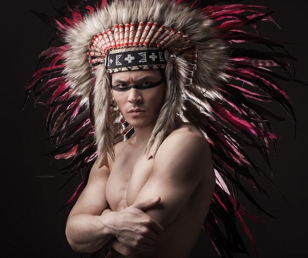 Homem forte indiano posando com maquiagem tradicional americana nativa