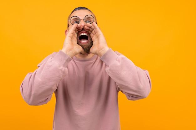 Homem forte irritado com cabelo preto curto grita isolado no fundo laranja