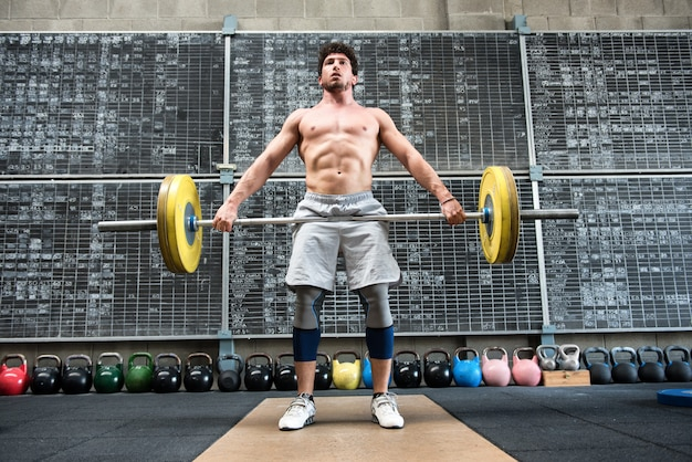 Homem forte, levantando barra pesada